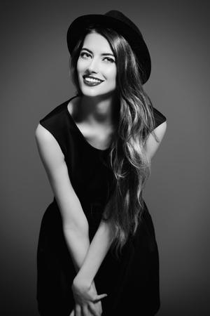 Gioiosa bella ragazza che indossa abito nero e cappello classico nero sorridente a porte chiuse. Bellezza, concetto di moda. Stile Hipster. Archivio Fotografico - 44968825