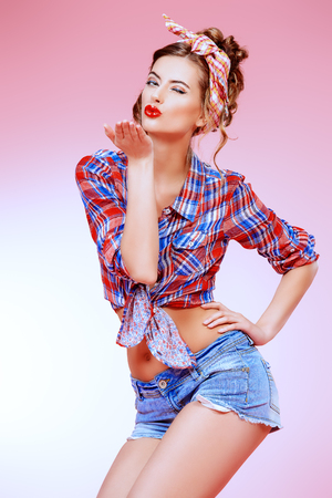 Attractive smiling pin-up girl alluring in shorts and shirt over pink background. Beauty, fashion.