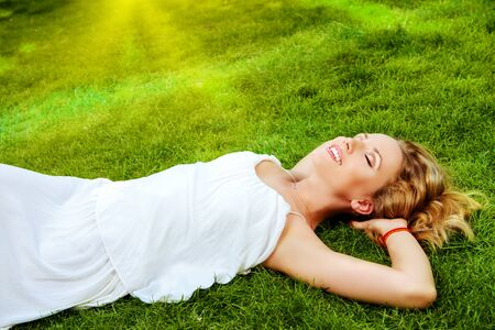 Beautiful smiling woman lying on a grass outdoor