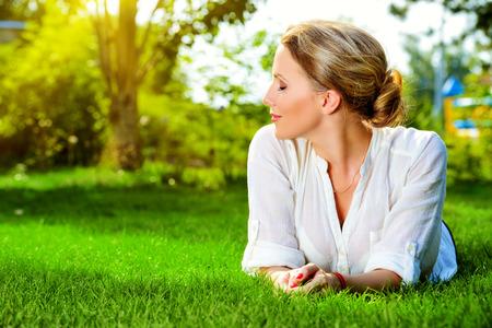 美しい笑顔の女性は、屋外の草の上に横たわる。彼女は、絶対に幸せです。