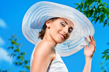 Portrait of a beautiful smiling woman in light white dress and elegant hat over blue sky Stock Photo
