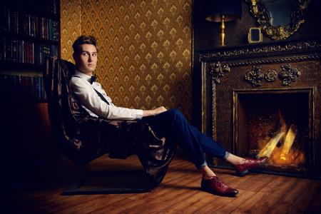 Elegant hübscher junger Mann sitzt am Kamin in einem Raum mit klassischen Vintage-Interieur Standard-Bild