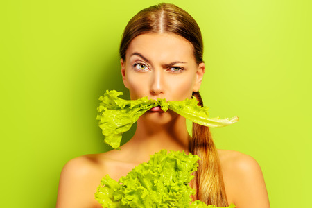 Pretty cheerful young woman posing with fresh green lettuce leaves