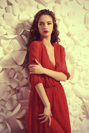 Gorgeous fashion model in bright red dress over background of white paper flowers
