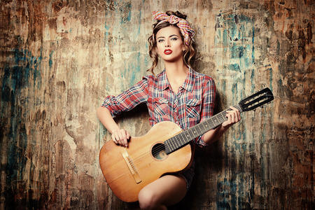 Pretty pin-up girl posing with guitar 版權商用圖片