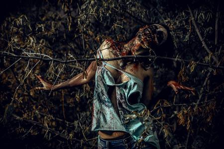 Horrible bloody zombie girl standing outdoor