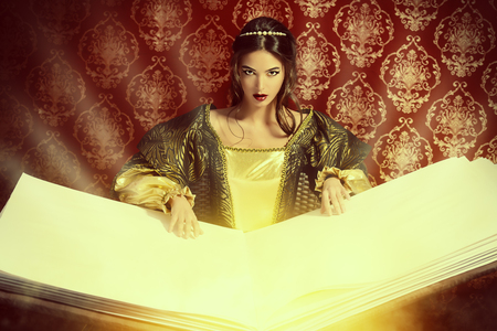 Fairy beautiful witch reads magic book of spells