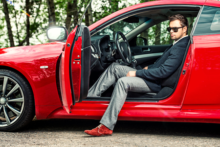 Handsome young man in his new sports car. Stockfoto