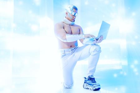 Stattlicher muskulöser Mann der Zukunft trägt futuristischen Brille arbeitet an einem Laptop. Technologien der Zukunft.
