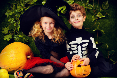 Funny boy and a girl wearing halloween costumes posing with pumpkins. Halloween.