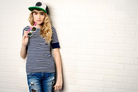 カジュアルな服とサングラスのれんが造りの壁、ポージングでうれしそうな十代の少女。アクティブなライフ スタイル。若者のファッション。スタ