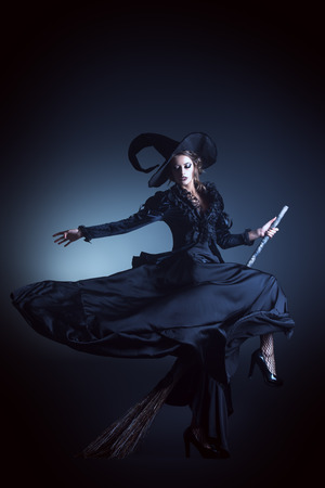 검정 배경 위에 빗자루 비행 화려한 갈색 머리 마녀의 초상화입니다. 할로윈. 스톡 콘텐츠