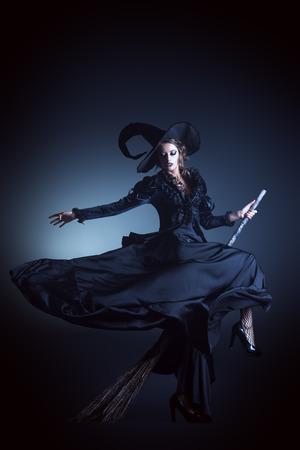 Portret van een schitterende brunette heks vliegen op een bezem op zwarte achtergrond. Halloween.
