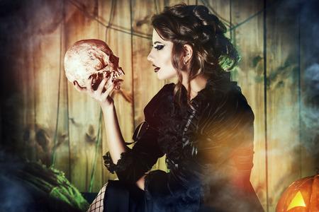 chica atractiva bruja en traje medieval que sostiene un cráneo en una casa abandonada mysteus. Brujería, bruja. Vampiro. Concepto de Halloween. Foto de archivo