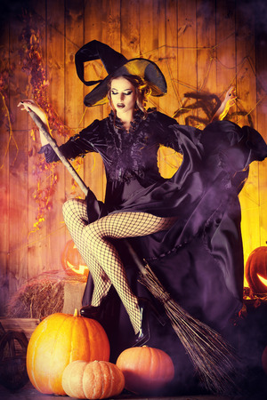 Beautiful fairy witch with her broom in a wooden barn with pumpkins. Halloween. Stock Photo