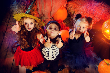 Three children dressed as a witch, a skeleton and a black cat celebrating halloween in a wooden barn with pumpkins. Halloween concept. Stock Photo