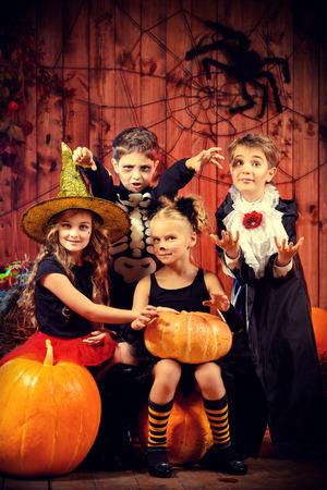 Vrolijke kinderen in Halloween kostuums vieren Halloween in een houten schuur met pompoenen. Halloween concept.