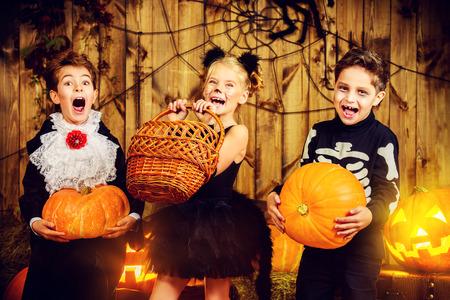 ハロウィーンのうれしそうな子供たちのグループは、カボチャと木造の納屋で一緒にポーズ衣装します。ハロウィンのコンセプトです。