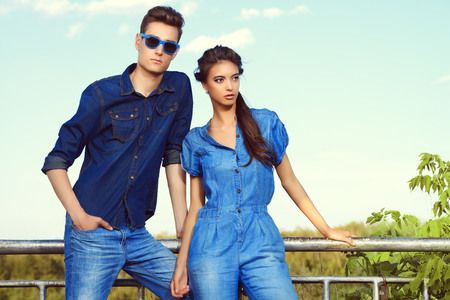 Fashion shot of an attractive young couple in jeans clothes posing outdoor.