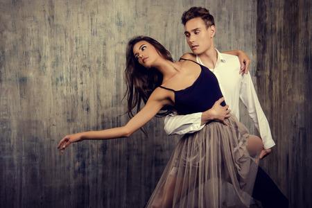 グランジ背景の上に踊るバレエ ダンサーの美しいカップル。美容、ファッション。