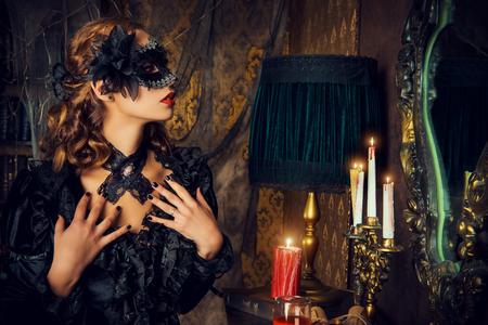 검은 마스크와 검은 중세 드레스에 매력적인 신비한 소녀 성 거실에 서있다. 흡혈귀. 할로윈 개념입니다. 빈티지 스타일.