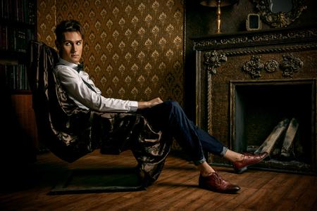 클래식 빈티지 인테리어 방에 벽난로에 앉아 우아한 잘 생긴 젊은 남자. 패션 샷. 스톡 콘텐츠