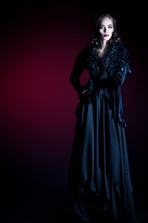 Volledige lengte portret van een prachtige vampier vrouw in zwarte middeleeuwse kleding over donkere bloedige achtergrond. Halloween. Stockfoto