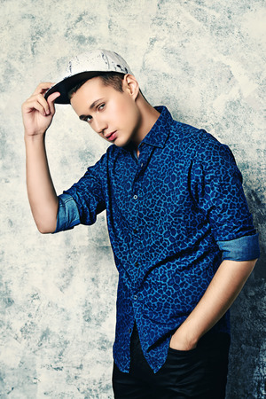 Portrait of a casual young man wearing jeans shirt and baseball cap.