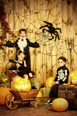 Group of joyful children in halloween costumes posing together in a wooden barn with pumpkins Stock Photo