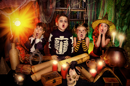 Group of frightened children dressed in halloween costumes in a wizarding lair