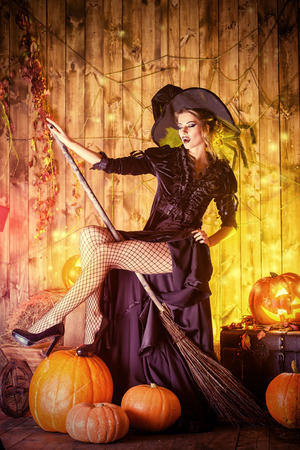 Beautiful fairy witch with her broom in a wooden barn with pumpkins