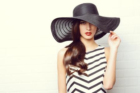 Portret van een mooie bevallige vrouw in elegante hoed met een brede rand