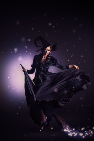 Portrait of a gorgeous brunette witch flying on a broom over black background
