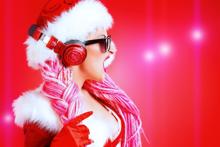 Awesome sexy Christmas girl in headphones. Red background Stock Photo