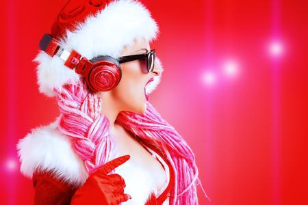 Impresionante Navidad chica sexy en auriculares. Fondo rojo Foto de archivo - 46291035