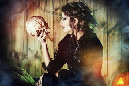 신비한 버려진 집에서 두개골을 들고 중세 드레스에 매력적인 마녀 소녀. 마법, 마녀. 흡혈귀. 할로윈 개념입니다. 스톡 콘텐츠 - 46564803
