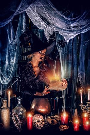 Aantrekkelijke heks tovert in de tovenaarswereld hol. Sprookjes. Halloween.