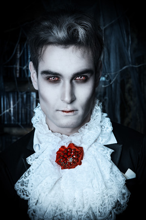 Handsome vampire man wearing elegant tailcoat stands in the old medieval castle. Halloween.