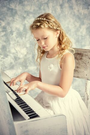 Beautiful eight year old girl in white dress playing the piano. Music and art concept. Vintage style. Stock Photo