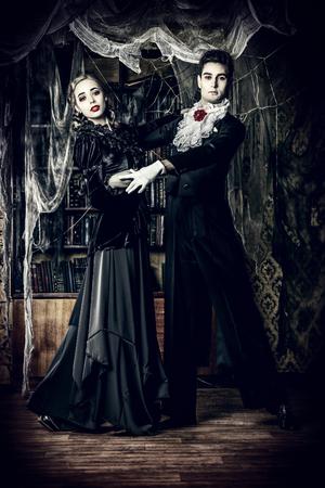 美しい男と女吸血鬼古い放棄された城の部屋で踊る中世の服を着ています。ハロウィーン。 写真素材