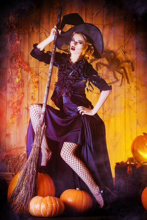 Mooie fee heks met haar bezem in een houten schuur met pompoenen. Halloween.