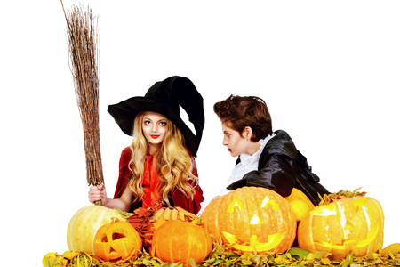 boy and girl teenagers wearing halloween costumes posing with pumpkins isolated over white autumn