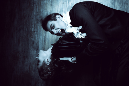 Bloodthirsty male vampire in medieval dress is biting a beautiful lady. Halloween.