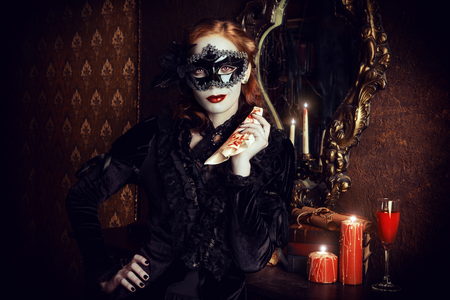 Charming mysterious girl in black mask and black medieval dress stands in a castle living room. Vampire. Halloween concept. Vintage style. Banco de Imagens - 46934549