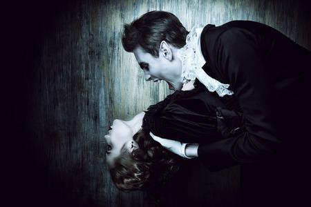 중세 드레스에 피에 굶주린 남성 뱀파이어 아름다운 여자를 물고있다. 할로윈.