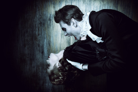 Bloodthirsty male vampire in medieval dress is biting a beautiful lady. Halloween. Banco de Imagens - 46934507
