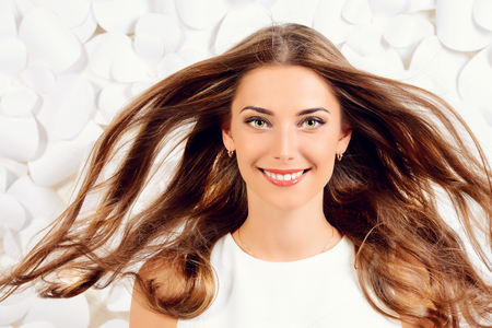 Smiling young woman with beautiful hair waving in the wind posing by a background of white paper flowers. Beauty, fashion. Haircare. Cosmetics.