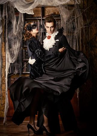 Schitterend paar vampiers gekleed in middeleeuwse kleding dansen in de oude verlaten kasteel. Halloween. Carnaval.