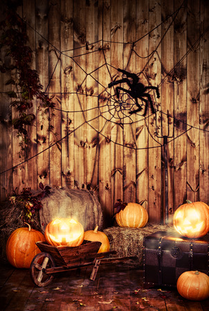 Halloween pumpkin head jack lantern in barn interior.