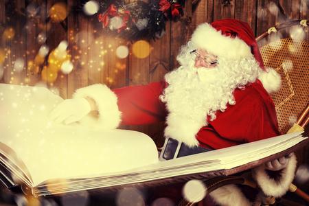 De Kerstman leest magisch boek in zijn houten huis. Stockfoto